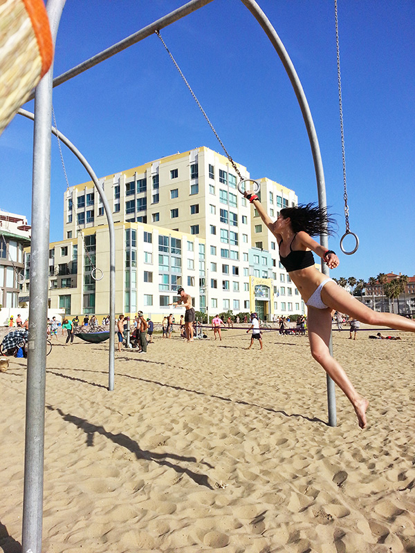 Girl swinging on bars in Santa Monica